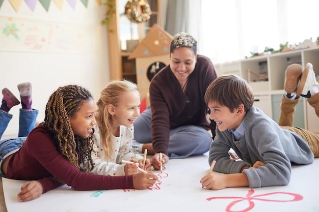 Портрет улыбающейся учительницы в полный рост, сидящей на полу с многоэтнической группой детей, рисующих картинки, наслаждаясь уроком искусства, копией пространства