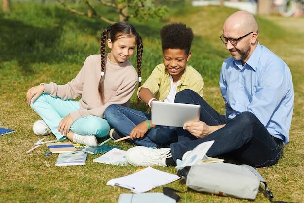 緑の芝生に座って、日光の下で野外授業を楽しんでいる間、子供たちと話している笑顔の男性教師の全身像