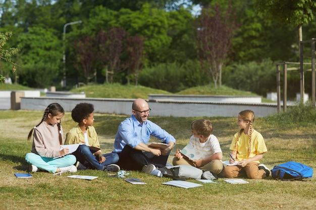 緑の芝生に座って、屋外のクラスを楽しんでいる間、子供たちのグループと話している笑顔の男性教師の全身像、コピースペース