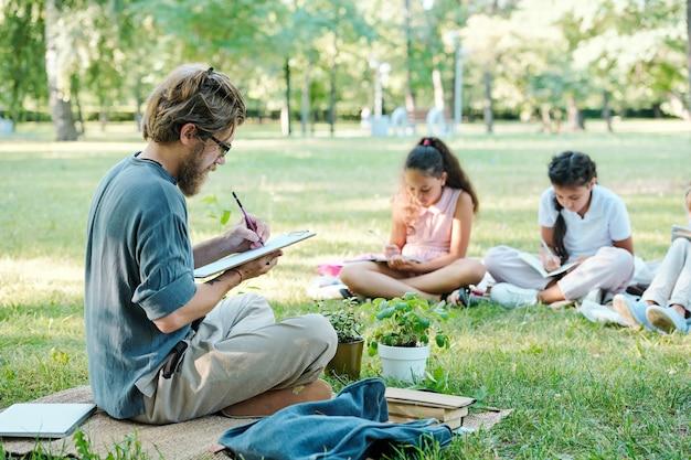 Портрет улыбающегося учителя-мужчины в полный рост, разговаривающего с группой детей, сидя на зеленой траве и наслаждающегося уроком на открытом воздухе при солнечном свете