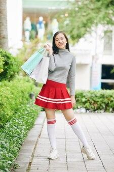 屋外に立っているときに買い物袋でポーズをとって笑顔の10代の少女の全身像
