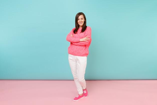 ニットのバラのセーター、白いズボンのポーズで笑顔の若い女性の完全な長さの肖像画