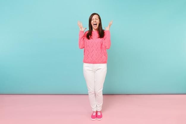 Портрет улыбающейся молодой женщины в полный рост в вязаном розовом свитере, позирует в белых штанах