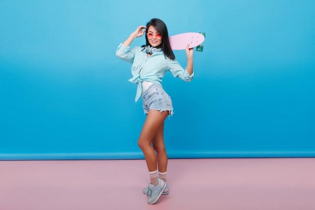 スポーティーな女の子のフルレングスの肖像画は、かわいい靴下とスタイリッシュな綿のシャツを着ています。青いインテリアの部屋で楽しんでいるスケートボードとスリムなブルネットのラテン女性。