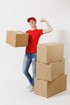 흰색 배경에 격리된 팔뚝, 근육을 보여주는 빨간 모자 티셔츠를 입은 강한 배달 여성의 전체 길이 초상화. 빈 판지 상자 근처에 서 있는 여성 택배. 패키지를 받고 있습니다. 복사 공간