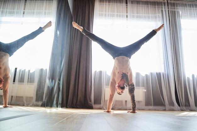 ダンスクラスの床でアクロバティックな要素を実行している黒いズボンの強いハンサムな男の完全な長さの肖像画