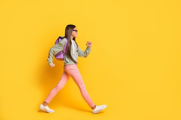 鮮やかな黄色の背景で隔離のスタイリッシュなパーカーを着て急いで歩く学生の完全な長さの肖像画