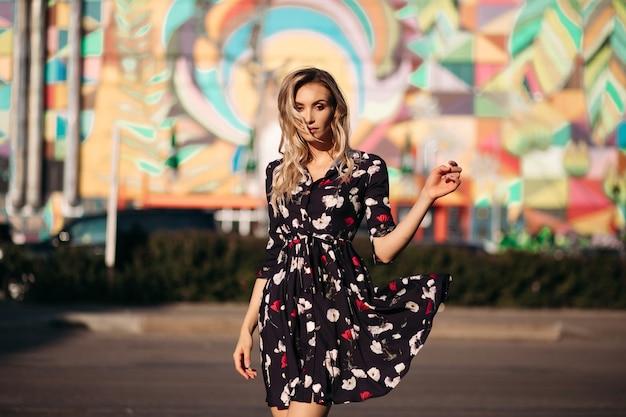 色付きの黒、白、赤のドレスと緑のかかとでポーズをとってスカートを手に、通りの明るい日差しの中で目を閉じてポーズをとっている見事な金髪の女性の全身像。色付きの背景。