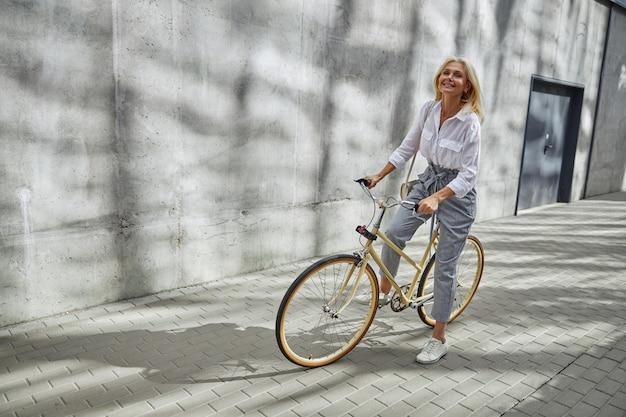 직장에 가는 동안 대도시에서 자전거로 생태 교통 수단을 사용하는 세련된 미모의 전체 길이 초상화
