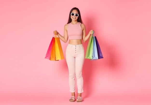 Портрет стильной, симпатичной азиатской женщины в полный рост, путешествующей за границу и покупающей сувениры