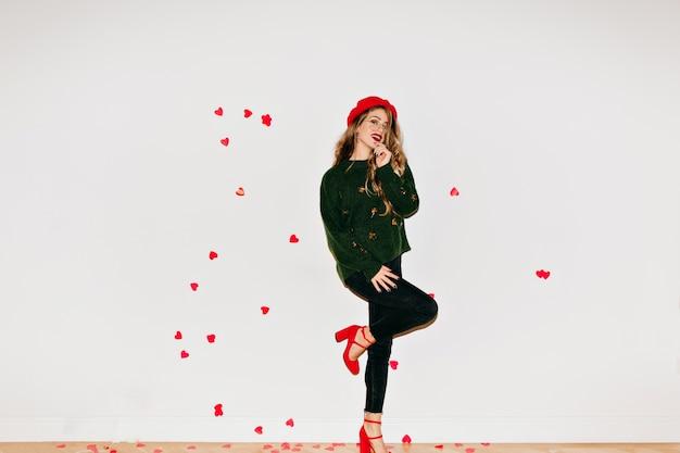 Портрет стильной женщины в полный рост, позирующей на одной ноге в светлой комнате, украшенной сердечками