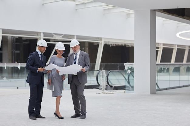 실내 건설 현장에 서있는 동안 계획을보고 성공적인 사업 사람들의 전체 길이 초상화,
