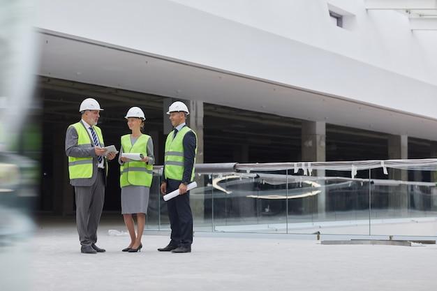 Hardhats를 착용하고 실내 건설 현장에 서있는 동안 투자 거래를 논의하는 세 명의 성공적인 사업 사람들의 전체 길이 초상화,