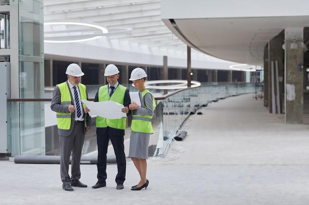 안전모를 착용하고 실내 건설 현장에 서있는 동안 계획을 검사하는 세 명의 성공적인 사업 사람들의 전체 길이 초상화,