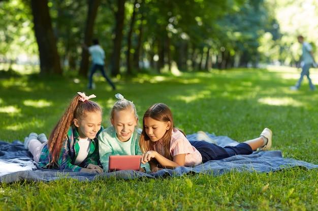 Портрет в полный рост трех девочек-подростков, использующих цифровой планшет, лежа на зеленой траве в парке на открытом воздухе, освещенном солнечным светом
