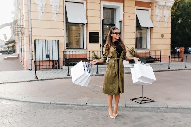 Портрет модной модницы в полный рост в элегантных туфлях на высоком каблуке и длинном пальто.