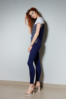 タイトな青いズボンに長い脚、ストライプと火の赤で描かれた髪の毛のtシャツとトレンディな内気な少女の完全な長さの肖像画。 Premium写真