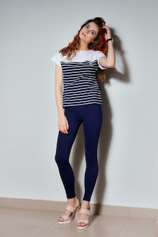 タイトな青いズボンに長い脚、ストライプと火の赤で描かれた髪の毛のtシャツとトレンディな内気な少女の完全な長さの肖像画。