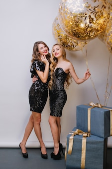 Портрет двух удивительных девушек в полный рост, готовящихся к дню рождения. крытое фото привлекательной европейской молодой женщины в черном платье, позирующей с сестрой, которая держит кучу воздушных шаров.