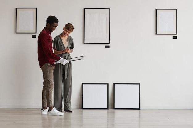 Портрет двух работников картинной галереи в полный рост, смотрящих на рамы для картин, планируя выставку в музее,