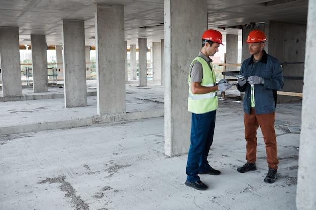建設現場に立ってプロジェクトについて話し合っている2人の建築請負業者の全身像、コピースペース