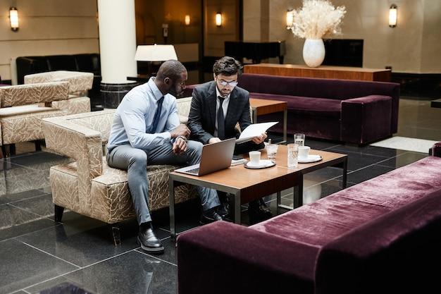 고급 호텔 로비에서 회의 중 작업에 대해 논의하는 두 사업가의 전체 길이 초상화, 복사 공간