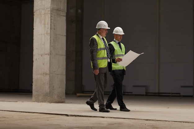 안전모를 착용하고 실내에서 건설 현장을 걷는 동안 계획을 잡고있는 두 비즈니스 사람의 전체 길이 초상화,