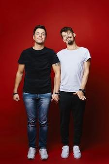 赤い背景で隔離の笑顔と手をつないでいる2人の陽気な若い男性の完全な長さの肖像画。