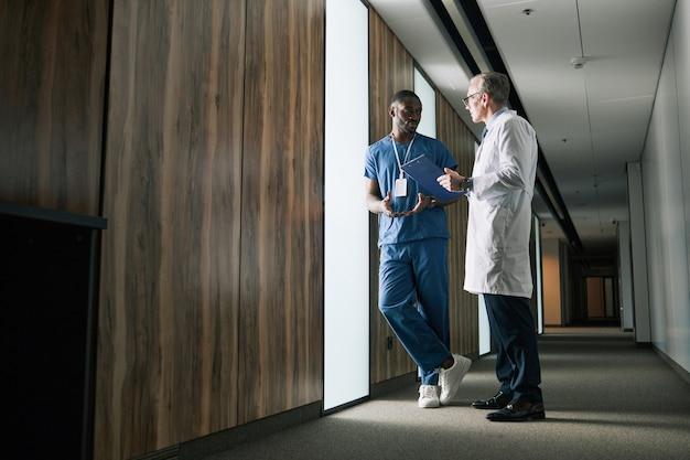 Полнометражный портрет двух врачей, говорящих, стоя в зале клиники, копией пространства
