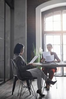 Портрет в полный рост двух элегантных деловых женщин, работающих вместе в графическом интерьере офиса, копией пространства