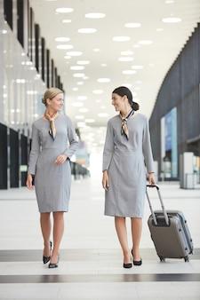 Портрет двух элегантных бортпроводников в полный рост, идущих к камере в аэропорту и весело улыбающихся