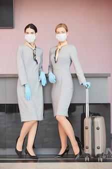 Портрет в полный рост двух элегантных бортпроводников в масках, стоящих у стойки регистрации в аэропорту и позирующих с чемоданом