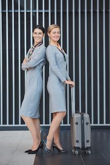 Портрет двух элегантных стюардесс в полный рост, улыбаясь в камеру, позируя с чемоданом на графическом фоне