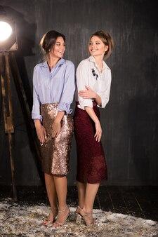 Портрет в полный рост двух счастливых улыбающихся молодых элегантных женщин в юбках с блестками как карандаш, блузка и высокие каблуки. студия моды выстрелил на черном фоне. вечернее платье или концепция праздничного платья