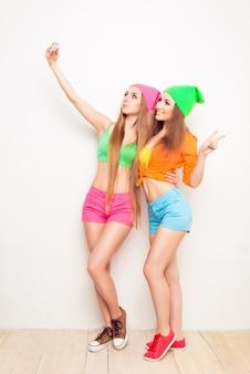Портрет двух хипстерских девушек в полный рост, делающих селфи