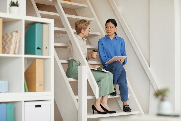Полнометражный портрет двух современных деловых женщин, сидящих на лестнице в офисе и болтающих, копируя пространство