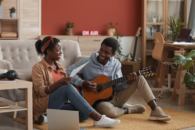 녹음 스튜디오에서 바닥에 앉아있는 동안 기타를 연주하고 함께 음악을 쓰는 두 젊은 아프리카 계 미국인 음악가의 전체 길이 초상화, 복사 공간