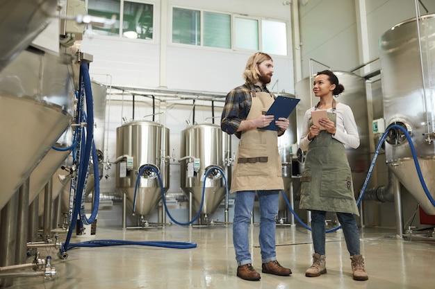 醸造所のワークショップ、コピースペースに立っている間、お互いを見つめているエプロンを身に着けている2人の若い労働者の完全な長さの肖像画