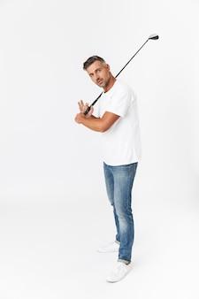 흰색으로 격리된 캐주얼 티셔츠를 입고 클럽을 들고 골프를 치는 깎지 않은 30대 남성의 전체 길이 초상화