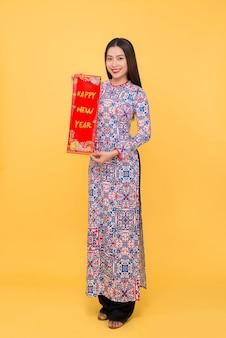 Портрет вьетнамской девушки в платье ао-дай в полный рост с новогодними свитками