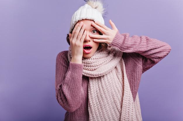 黒のパンストで身なりのよい女の子の全身像は、緑豊かなスカートで遊ぶ。紫色の壁にポーズをとって長いスカーフとセーターのかわいい女性の屋内写真。