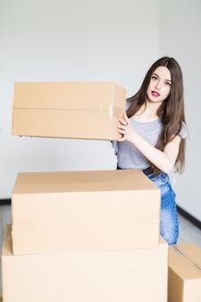 Портрет женщины в полный рост, несущей картонную коробку в новом доме