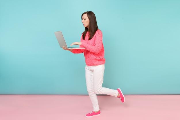 Портрет в полный рост женщины в вязаном розовом свитере, белых штанах, использующих портативный компьютер