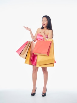 Полный портрет женщины в розовом платье с хозяйственными сумками, изолированными на белом фоне