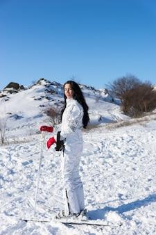 Портрет в полный рост женщины с длинными темными волосами в белом лыжном костюме и лыжах, стоящей на заснеженной горе и оглядывающейся через плечо на камеру в день с ярким солнцем