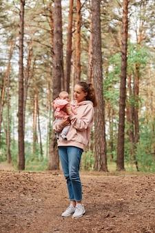 幼児の女の子を手にした若い成人女性の全身像