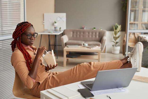持ち帰り用の食べ物を食べて、ホームオフィスでリラックスしながらノートパソコンの画面を見ている若いアフリカ系アメリカ人女性の全身像、コピースペース