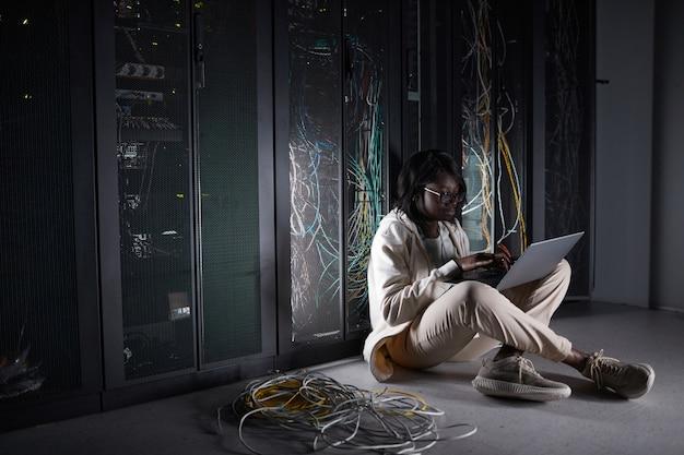 Портрет молодой афро-американской женщины в полный рост, сидящей на полу в серверной и использующей ноутбук во время работы с суперкомпьютером в центре обработки данных, копией пространства