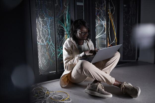 Портрет молодой афро-американской женщины в полный рост, сидящей на полу в серверной и использующей ноутбук во время работы с суперкомпьютером в центре обработки данных
