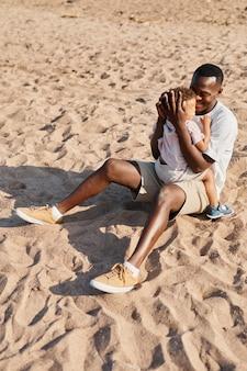 ビーチtogeで砂で遊んでいる間息子を保持している若いアフリカ系アメリカ人の父の完全な長さの肖像画...